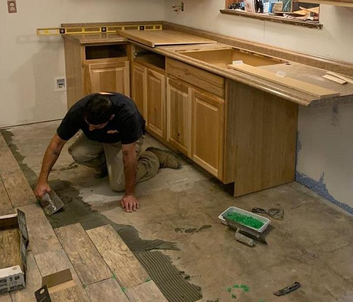 Technician replacing carpet with tile